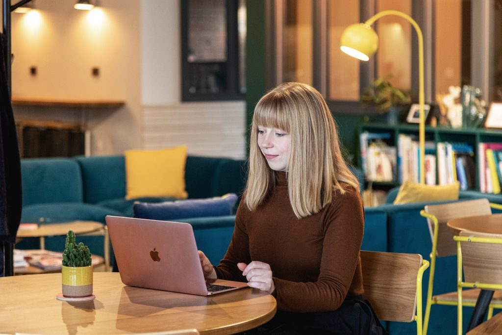 Gather round member Harriet Wilson working on laptop in the lounge